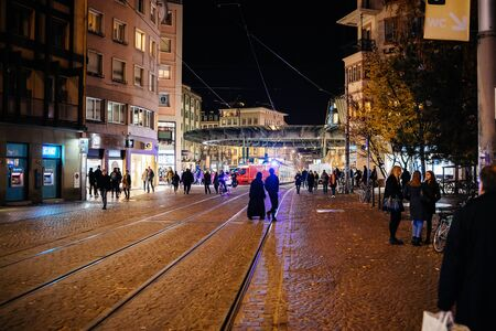 Strasbourg, France - Nov 23, 2017: Pedestrians walking at night in Place de l'Homme de Fer in central Strasbourg the main tramway station in Alsace Capital