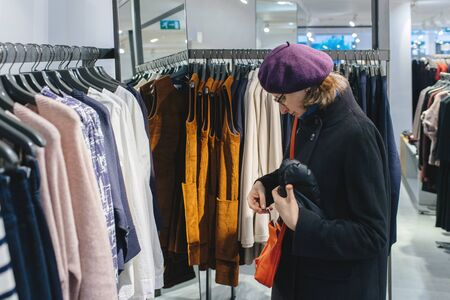 Beautiful French woman wearing purple beret hat looking at the orange leather purse in fashionable clothing store Фото со стока