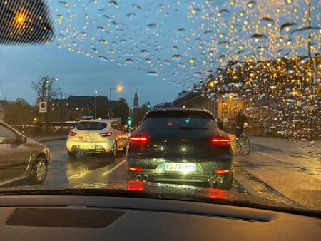 Strasbourg, France - Oct 17, 2019: View through the rainy windshield of a car at the cars driving on main avenue on a cold fall day in central Strasbourg Redactioneel