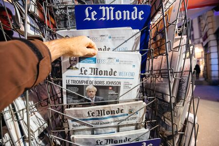 Paris, France - Dec 14, 2019: POV Man buy press kiosk the latest Le Monde newspaper day after UK Prime Minister Boris Johnsons Conservative Party won Early General Parliamentary victory