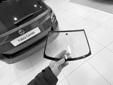 Paris, France - Oct 25, 2019: Man hand holding miniature glass windshield inside car auto repair shop center near Skoda Octavia Combi car black and white image Redactioneel