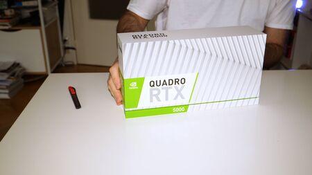 Paris, France - Mar 11, 2019: Curious man before unpacking new Nvidia Quadro RTX 5000 for workstations running professional CAD, CGI, DCC application software video card GPU 에디토리얼