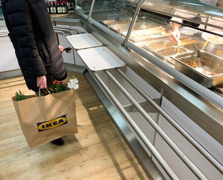 Paris, France - Dec 1, 2018: Side view of unrecognizable woman waiting in queue at the counter of IKEA restaurant waiting to place the order for swedish meatballs Redactioneel