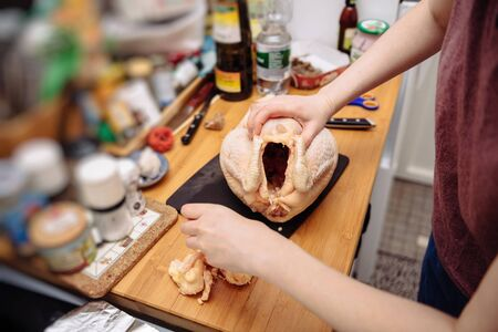 Woman removing fat from fresh Capon Chapon cockerel meat on kitchen wooden top French organic eco bio meat for the Christmas Winter holiday cuisine