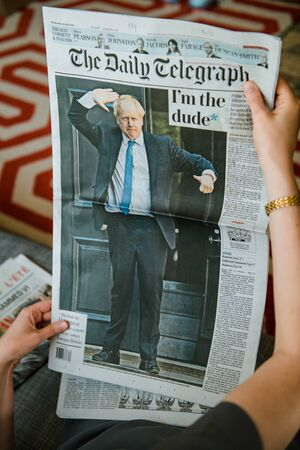 Paris, France - Jul 24, 2019: POV woman hand holding reading newspaper with Boris Johnson appears on cover of the Daily Telegraph as he becomes UK United Kingdom Prime Minister - im the dude title 에디토리얼