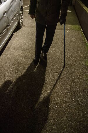 Front view of silhouette of senior man walking on French street at night using walking stick preserving equilibrium with blue telescopic aluminum cane Medical assistance and rehabilitation 스톡 콘텐츠