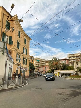 Sanremo, Italy - Nov 22, 2019: Car on the rondo G. Garibaldi roundabout with multiple shops, restaurant cars and clear blue sky