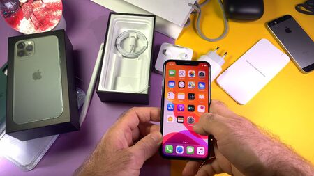 Paris, France - Sep 20, 2019: Home screen apps POV man hand unboxing unpacking highly acclaimed new Apple Computers iPhone 11 Pro and 11 Pro Max smartphone triple-lens camera