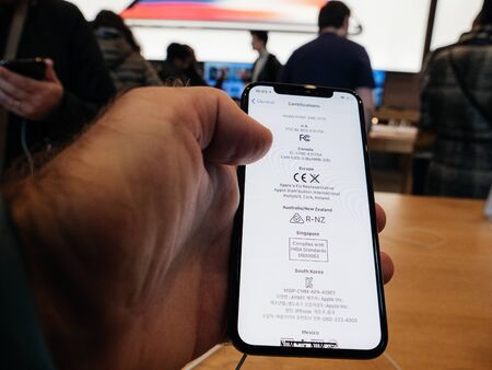 Paris, France - Nov 3, 2017: POV of male hand customer admiring inside Apple Store the latest professional iPhone smartphone manufactured by Apple Computers and certifications of the headset