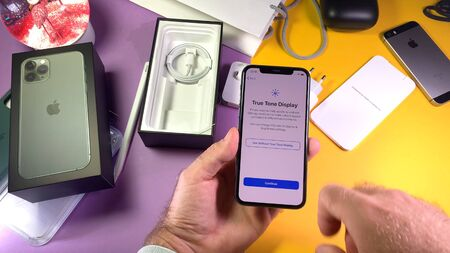 Paris, France - Sep 20, 2019: True tone display settings POV man hand unboxing unpacking highly acclaimed new Apple Computers iPhone 11 Pro and 11 Pro Max smartphone triple-lens camera