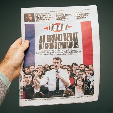 Paris, France - Mar 15, 2019: Male hand POV at the latest Liberation edition of newspaper featuring Emmanuel macron grand debat breaking news Editorial