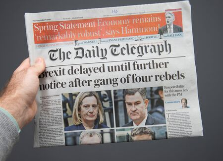 Paris, France - Mar 15, 2019: Male hand POV at the latest THe Daily Telegraph edition of newspaper featuring breaking news about delayed brexit
