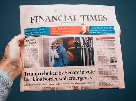 Paris, France - Mar 15, 2019: Male hand POV at the latest edition of Financial Times newspaper featuring breaking news about Brexit, Theresa may and Trump rebuked by Senate