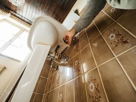 Low angle view of manual worker removing the old sink in vintage old bathroom Reklamní fotografie