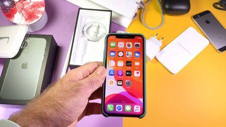 Paris, France - Sep 20, 2019: Holding phone in protection case POV man hand unboxing unpacking highly acclaimed new Apple Computers iPhone 11 Pro and 11 Pro Max smartphone triple-lens camera
