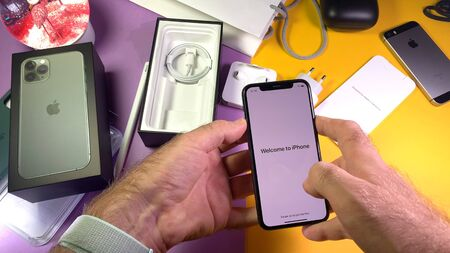 Paris, France - Sep 20, 2019: Welcome to iPhone message POV man hand unboxing unpacking highly acclaimed new Apple Computers iPhone 11 Pro and 11 Pro Max smartphone triple-lens camera