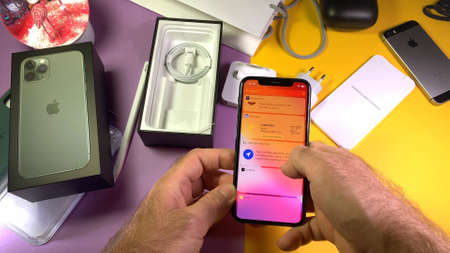 Paris, France - Sep 20, 2019: Shortcuts app menu POV man hand unboxing unpacking highly acclaimed new Apple Computers iPhone 11 Pro and 11 Pro Max smartphone triple-lens camera