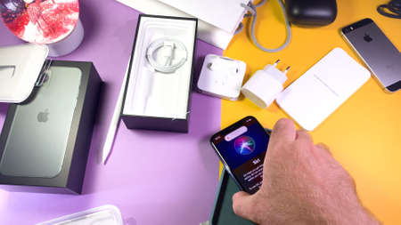 Paris, France - Sep 20, 2019: Man put on table phone with Siri menu POV man hand unboxing unpacking highly acclaimed new Apple Computers iPhone 11 Pro and 11 Pro Max smartphone triple-lens camera 에디토리얼