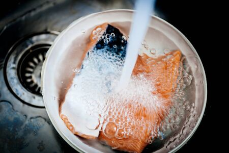 Clean water pouring washing inside kitchen stainless steel sink with plastic bowl containing two pieces of fresh bio organic salmon fish 写真素材