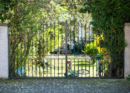 Closed beautiful forged steel gate entrance to luxury garden with multiple bicycles parked behind