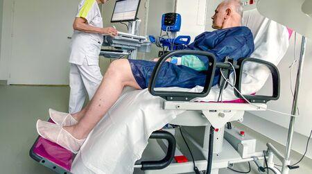 Sitting senior male on modern medical chair inside modern hospital in France resting after infection virus coronavirus optimistic view and nurse preparing data