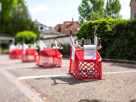 Strasbourg, France - Apr 13, 2020: Tilt-shift lens view over delimitation barrier of supermarket carts in the large parking area of modern food mall store during Covid-19 coronavirus pademy - do not park sign