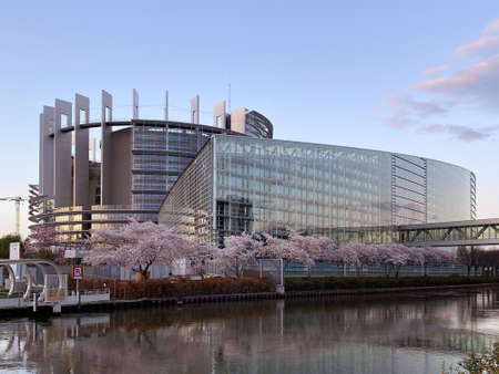 Strasbourg, France - March 14, 2020: Wide angle view of European Parliament in Strasbourg with in bloom sakura tree blue clear sky and calm ill river Editorial