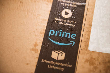 Lyon, France - Aug 7, 2019: Fresh delivery Wet Amazon Prime parcel cardboard with multiple water drops being delivered under rainy weather
