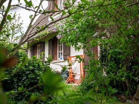 View from the garden at old beautiful French house with construction with orange trestles near the entrance Фото со стока