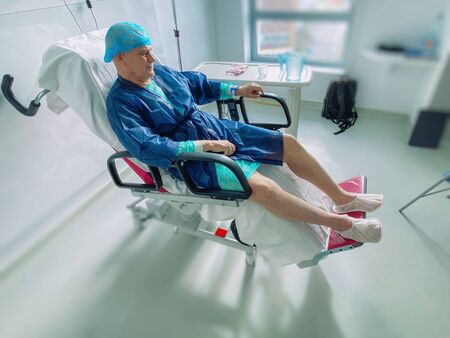 Happy smiling senior man - elevated view of lying on the medical chair senior male inside modern hospital in France resting after infection virus coronavirus