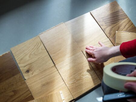 Overhead view of architect woman hand touching the wooden surface of multiple natural wooden floor parquet before deciding which one to buy