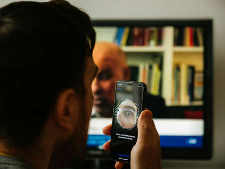 Paris, France - Nov 10 2017: Eye in the screen camera Man setting new Apple iPhone XS Pro with Face ID virtual facial recognition function data monitor in the background