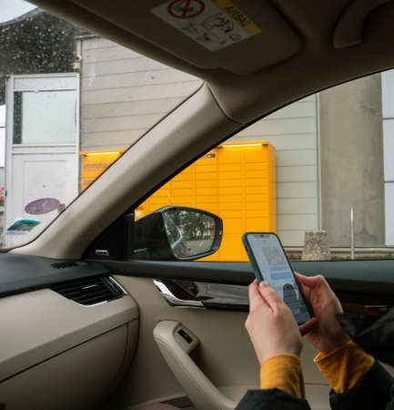 Paris, France - Mar 29, 2020: Square image woman inside luxury car in front of yellow Amazon Locker holding smartphone remembering access code to retrieve the parcel Redactioneel