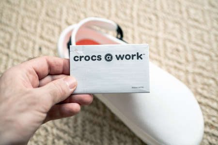 Paris, France - Dec 13, 2020: POV male hand holding paper advertising tag of Crocs at work comfortable shoes with price advertising etiquette