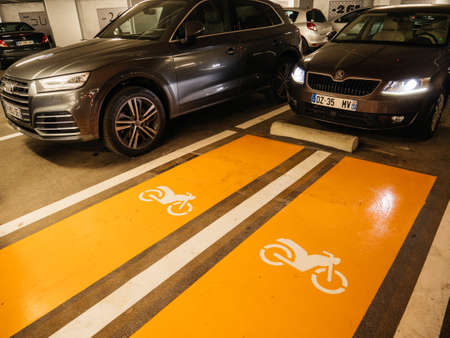 Strasbourg, France - Jan 7, 2021: Skoda and Audi SUV cars parked inside underground parking with two special places for motorcycle