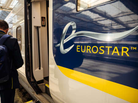 London, United Kingdom - May 18, 2018: Rear view of passenger male with backpack entering the large door of the Eurostar train in St Parnas train station with estination Paris France