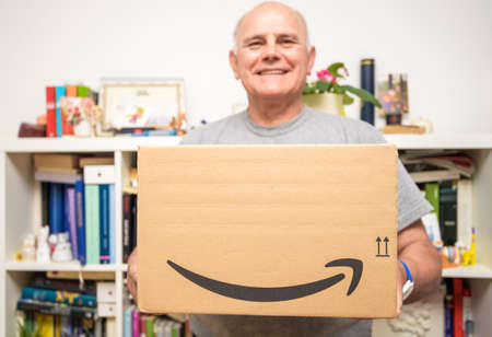 Paris, France - Oct 10, 2019: Happy Senior man smiling while holding new Amazon Prime parcel logotype with the smiling arrow - the internet congolomerat founded by Jeff Bezos in a home garage in 1994