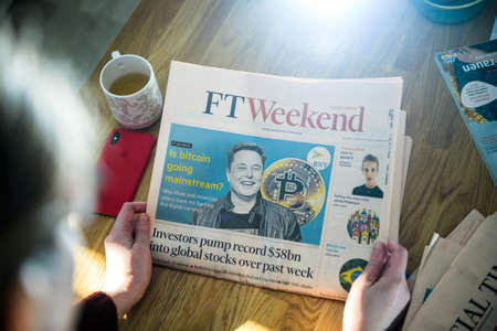 Paris, France - FEb 13, 2021: POV business woman reading Financial Times newspaper on kitchen counter with Elon Musk headline smiling and text Is bitcoin going mainstream