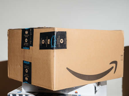 PAris, France- Jan 23, 2021: Close-up of well pretected by scotch tape Amazon Prime cardboard box parcel - the on-line retailer giant was founded by Jeff Bezos