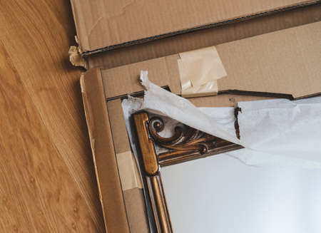 Close-up view of vintage wooden luxury framed mirror delivered without any flaws in the cardboard package - security safety during transportation fragile objects