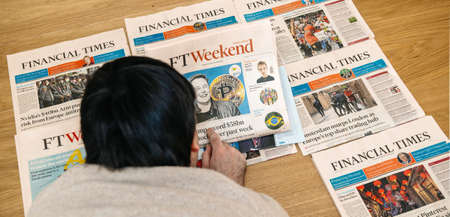 Paris, France - Feb 13, 2021: Overhead view of young man reading on the wooden floor multiple Financial Times newspapers with diverse headlines with Elon Musk and bitcoin cryptocurrency