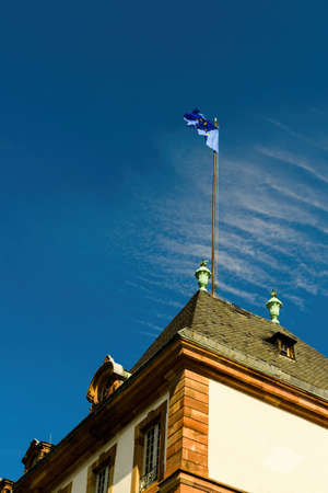 Low angle view of waving tall European Flag - the Council of Europe and the European Union as a symbol representing Europe - clear blue sky in the background and beautiful rooftop