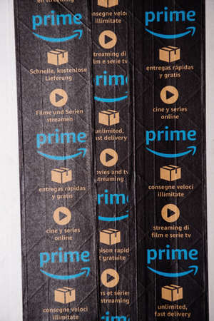 Paris, France - Jan 23, 2021: Vertical image of multiple lines of Amazon Prime scotch tape on the cardboard of a parcel with Prime advertising for fast delivery and streaming tv