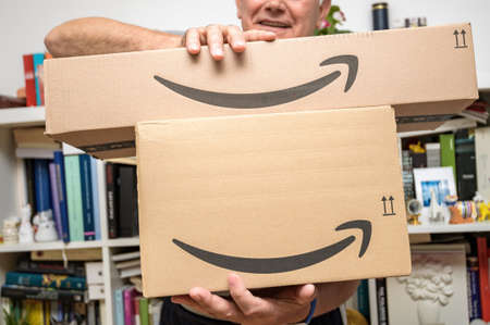Senior man holding two new Amazon Prime parcel logotype with the smiling arrow - the internet congolomerate founded by Jeff Bezos founding Amazon in a home garage in 1994