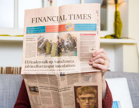 Woman reading in living room next to her cat the latest Financial Times