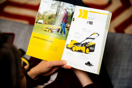 Curious woman reading latest advertising catalogue of Karcher German Éditoriale