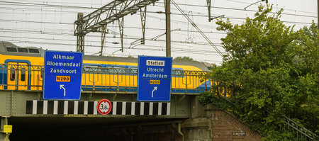 Fast Dutch train passing on the bridge with guidance signage street sign to Alkmaar, Bloemendaal, Zandvoort and direction to station with destination to Utrecht and Amsterdam