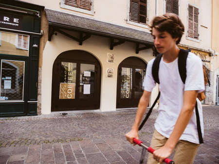 Silhouette of French boy on electric scooter discovering the city of Chambery