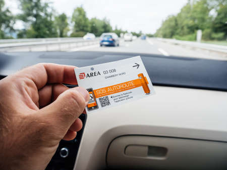Driver male hand holding inside car ticket of Toll Road operated by Area Éditoriale