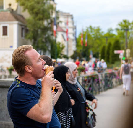 Adult male licking eating delicious ice-cream cone with women in background